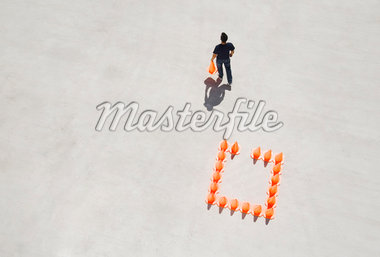 Man walking away from box of traffic cones with one Stock Photo - Premium Royalty-Freenull, Code: 635-01489224