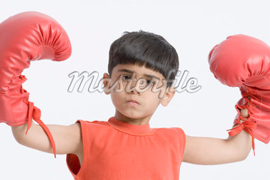 Portrait of a boy wearing boxing gloves and flexing his muscles Stock Photo - Premium Royalty-Freenull, Code: 630-01491817