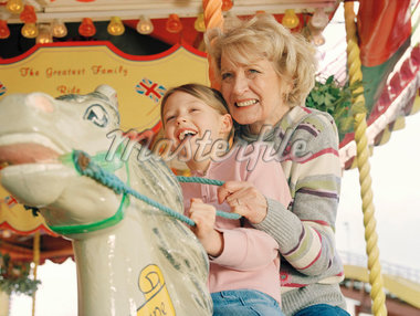 Grandmother on carousel horse with granddaughter (7-9) smiling Stock Photo - Premium Royalty-Freenull, Code: 613-01522793