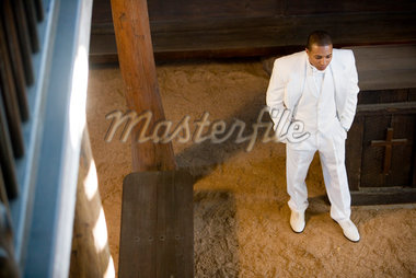Elevated view of a groom in a white tuxedo pacing with hands in pockets Stock Photo - Premium Royalty-Freenull, Code: 638-01584269