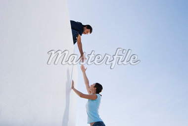 A man helping a woman climb a wall Stock Photo - Premium Royalty-Freenull, Code: 635-01594255