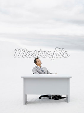 A businessman in the middle of nowhere at his desk Stock Photo - Premium Royalty-Freenull, Code: 635-01594456