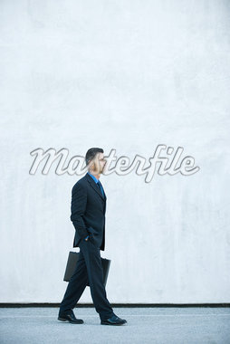 Businessman carrying briefcase, hand in pocket, full length Stock Photo - Premium Royalty-Freenull, Code: 632-01612906