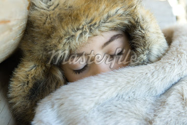 Preteen girl, wearing fur hat, sleeping under fur blanket, close-up Stock Photo - Premium Royalty-Freenull, Code: 632-01613102
