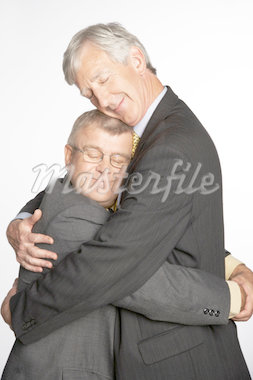 Tall and short businessmen hugging, side view Stock Photo - Premium Royalty-Freenull, Code: 613-01730325