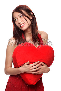 Young woman holding red heart shaped pillow, looking away Stock Photo - Premium Royalty-Freenull, Code: 656-01765615