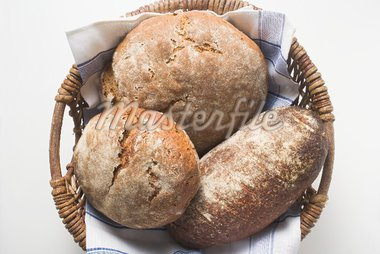 Three rustic loaves of bread in a bread basket Stock Photo - Premium Royalty-Freenull, Code: 659-01866609