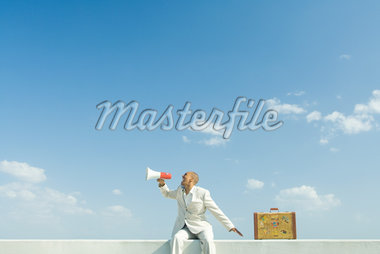 Man sitting on wall beside suitcase, shouting into megaphone Stock Photo - Premium Royalty-Freenull, Code: 633-01992494