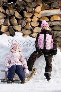 Young girls posing with sledge on snow Stock Photo - Premium Royalty-Freenull, Code: 649-02053544