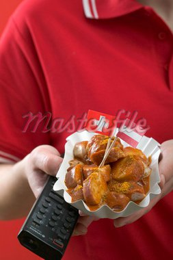 Footballer holding currywurst (sausage with curry sauce) & remote Stock Photo - Premium Royalty-Freenull, Code: 659-02213140