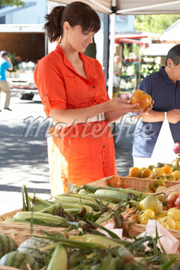 Woman Inspecting Vegetables at Local Market, Granville Island, Vancouver, British Columbia    Stock Photo - Premium Rights-Managed, Artist: Sarah Murray, Code: 700-02377505