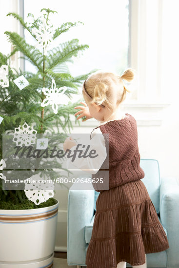 Little Girl Decorating a Christmas Tree With Paper Snowflakes Stock Photo - Royalty-Free, Artist: Michael Alberstat, Code: 600-02645625