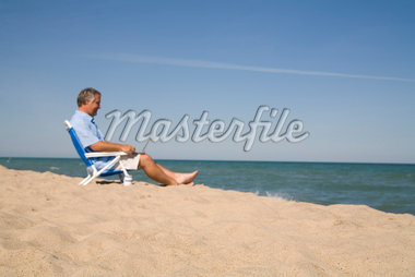 Man Sitting on the Beach Using Laptop Computer, Lake Michigan, USA Stock Photo - Premium Royalty-Free, Artist: Chris Karges, Code: 600-02757025