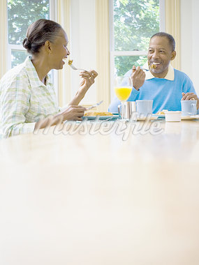 Senior woman with a senior man sitting at the breakfast table Stock Photo - Premium Royalty-Freenull, Code: 640-02764580
