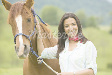 Portrait of a woman holding the reins of a horse Stock Photo - Premium Royalty-Freenull, Code: 640-02767471