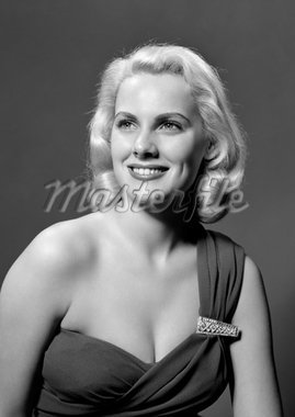 1950s WOMAN PORTRAIT WEARING ASYMMETRIC DRESS WITH RHINESTONE CLASP LOOKING OFF CAMERA SMILING INDOOR    Stock Photo - Premium Rights-Managed, Artist: ClassicStock, Code: 846-02793024