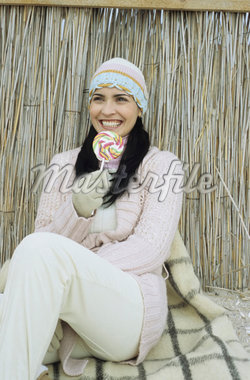 Darkhaired young Woman with a crocheted Hat holding a Lollipop - Sweets - Season Stock Photo - Premium Royalty-Freenull, Code: 628-02954680