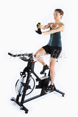Woman Riding Stationary Bicycle                                                                                                                                                                          Stock Photo - Premium Rights-Managed, Artist: Angus Fergusson          , Code: 700-03004431