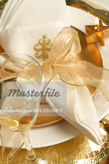 Christmas table place setting,napkin tied with a golden ribbon and a glass of white wine Stock Photo - Royalty-Freenull, Code: 689-03126873
