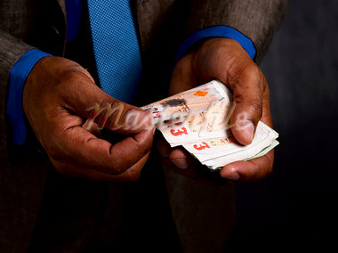 Business man with wad of sterling notes Stock Photo - Premium Royalty-Freenull, Code: 649-03293588