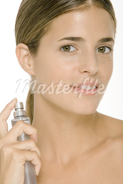 Woman putting on perfume, smiling at camera Stock Photo - Premium Royalty-Freenull, Code: 696-03402358