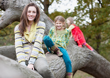 Mother and daughters climbing on tree branch Stock Photo - Premium Royalty-Freenull, Code: 635-03457379