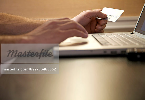 Close up of a man's hands holding a credit card and typing on a keyboard Stock Photo - Premium Rights-Managed, Artist: ableimages, Code: 822-03485552