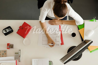 Businesswoman at desk busy with paperwork Stock Photo - Premium Royalty-Freenull, Code: 632-03500822