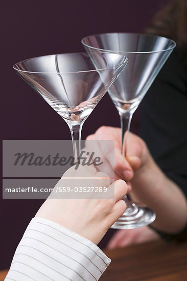 Hands clinking empty cocktail glasses Stock Photo - Premium Royalty-Freenull, Code: 659-03527289