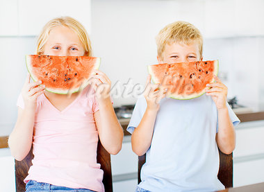Children holding watermelon slice in front of face Stock Photo - Premium Royalty-Freenull, Code: 635-03577410