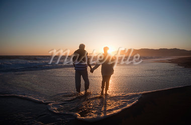 Senior couple holding hands on beach at sunset Stock Photo - Premium Royalty-Freenull, Code: 635-03577866