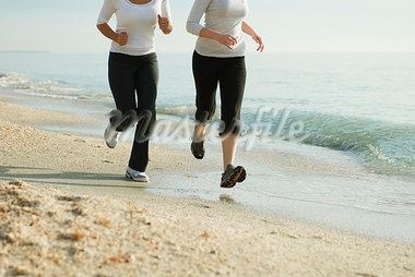 Female friends running at the beach, cropped Stock Photo - Premium Royalty-Freenull, Code: 632-03651839
