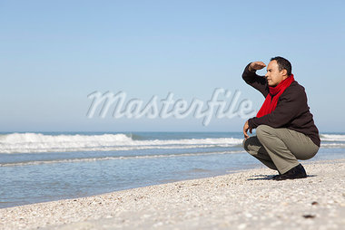 Man crouching on beach, looking at ocean Stock Photo - Premium Royalty-Freenull, Code: 632-03652073
