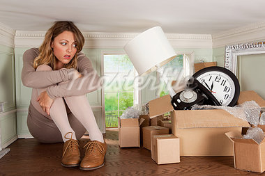 Young woman with box of objects in small room Stock Photo - Premium Royalty-Freenull, Code: 614-03684584