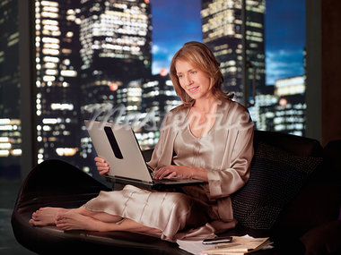 Woman in nightgown using laptop at night Stock Photo - Premium Royalty-Freenull, Code: 635-03685492