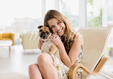 Smiling woman holding cute, small dog on lap Stock Photo - Premium Royalty-Freenull, Code: 635-03685506