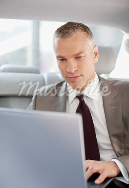 Businessman using laptop in back seat of car Stock Photo - Premium Royalty-Freenull, Code: 635-03685700