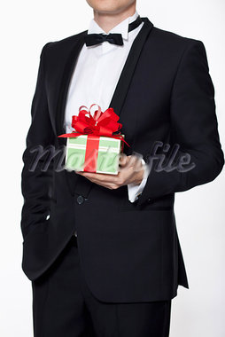 A man in a tuxedo holding a birthday gift, midsection Stock Photo - Premium Royalty-Freenull, Code: 653-03706818