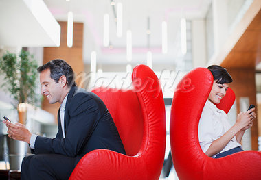 Business people text messaging on cell phones in lobby Stock Photo - Premium Royalty-Freenull, Code: 635-03752711