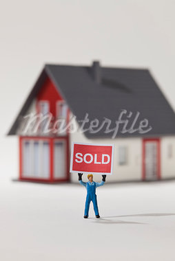 A miniature construction worker figurine holding aloft a SOLD sign Stock Photo - Premium Royalty-Freenull, Code: 653-03843560