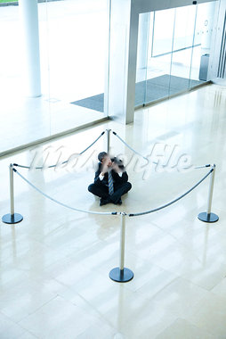 Businessman sitting on floor inside roped off area in lobby Stock Photo - Premium Royalty-Freenull, Code: 632-03848157