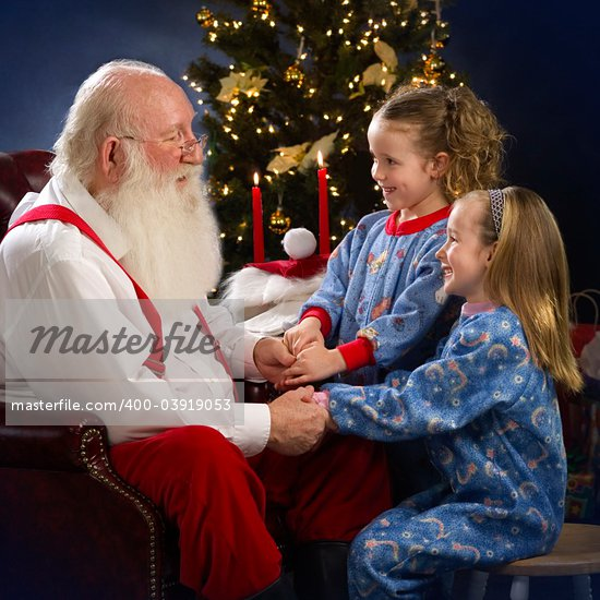 Santa Claus talking with two young girls in pajamas, christmas decorations in background, indoor studio shot, square format, focus on foreground Stock Photo - Royalty-Free, Artist: scotthancock, Code: 400-03919053