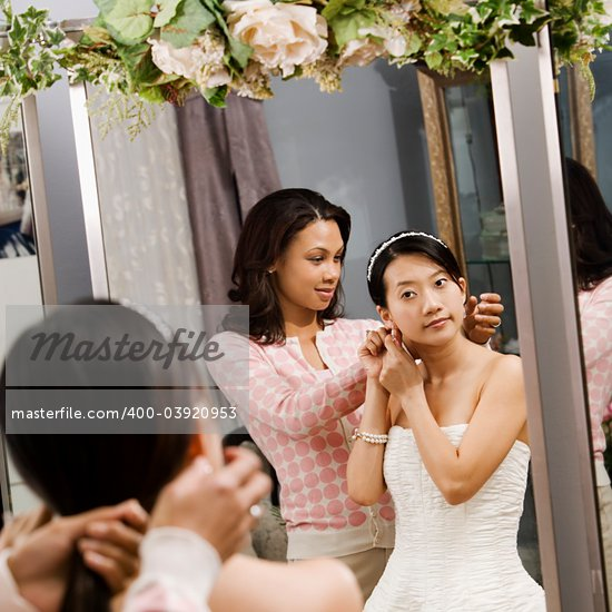 African-American woman helping Asian bride with hair. Stock Photo - Royalty-Free, Artist: iofoto, Code: 400-03920953