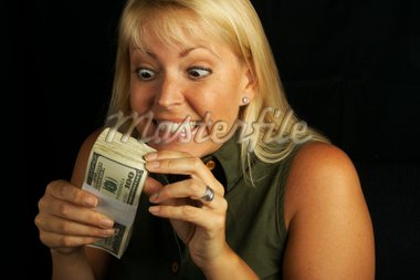 Attractive Woman Excited About her Stack of Money on a Black Background Stock Photo - Royalty-Free, Artist: Feverpitched, Code: 400-03929042