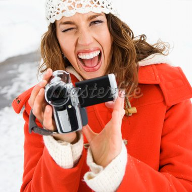 Caucasian young adult female in winter clothing pointing digital camera at viewer and winking. Stock Photo - Royalty-Free, Artist: iofoto, Code: 400-03937686