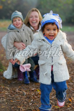 A beautiful mixed race girl runs towards the camera laughing while over her shoulder you see a young mother with her son. Stock Photo - Royalty-Free, Artist: darrenbaker, Code: 400-03943560