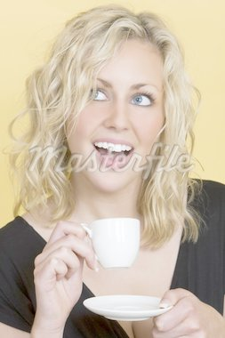 Studio shot of a beautiful young blonde woman drinking tea/coffee and laughing Stock Photo - Royalty-Free, Artist: darrenbaker, Code: 400-03956042