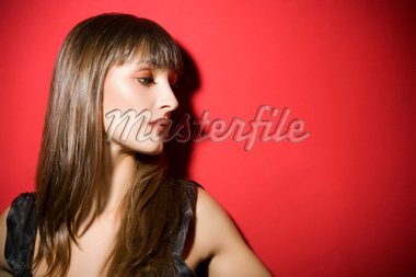 attractive girl standing against a red wall. Copy space on the right Stock Photo - Royalty-Free, Artist: diego_cervo, Code: 400-03970333