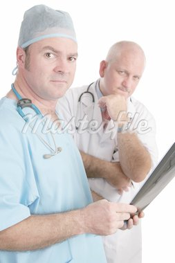 Two doctors examining xrays.  They are looking at the camera with serious expressions. Stock Photo - Royalty-Free, Artist: lisafx, Code: 400-03972477