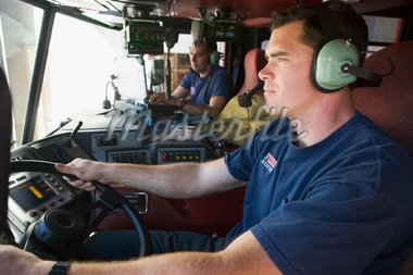 A firefighter driving a fire engine Stock Photo - Royalty-Free, Artist: MonkeyBusinessImages, Code: 400-04036431